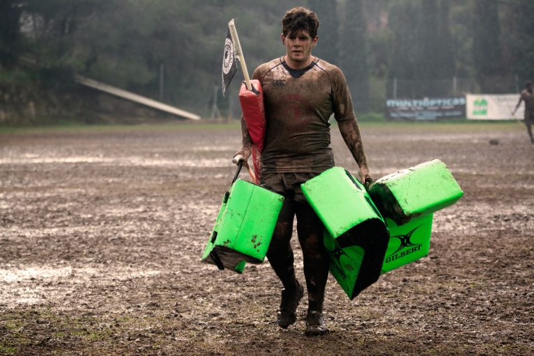 Man covered in mud carrying rugby equipment