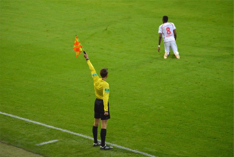 Assistant referee in football holding up his flag