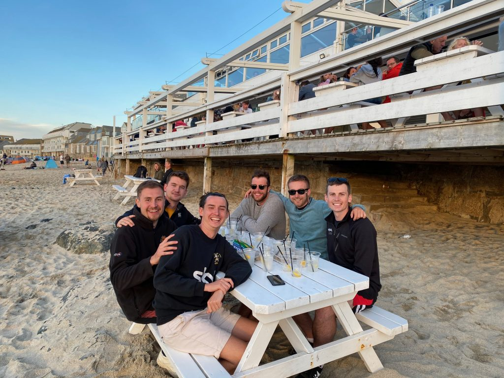 Me and five friends sat together on a bench on the beach.