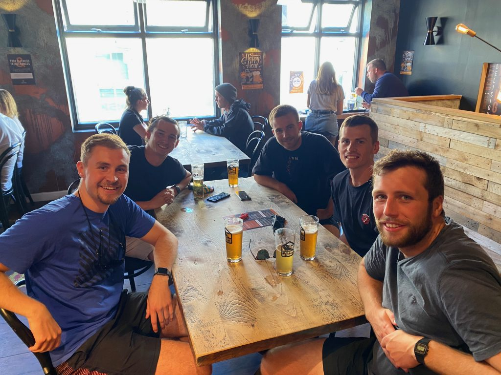 5 people sat around a table in a bar